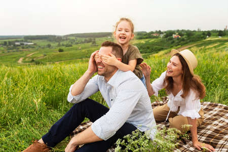 Little daughter closes her fathers eyes with hands from behind, sitting on the grass 写真素材