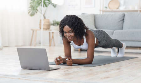 Well fit black girl planking at living room, looking at laptop screen, watching online fitness lessons, free space