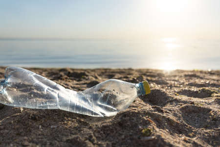 Wasted Single-Use Plastic Bottle Trash Lying On Beach Polluting Environment Outdoors. Polluted Coastline Concept. Free Space 免版税图像