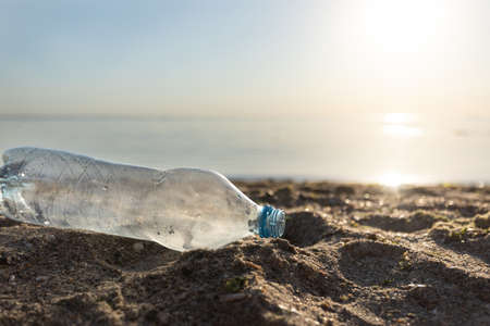 Sea Pollution Concept. Wasted Plastic Bottle Lying On Sand Seashore Beach Near Water. Ecological Background With Free Space For Text