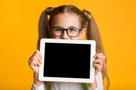 Schoolgirl Showing Tablet Computer Empty Screen Over Yellow Background. Mockup, Studio Shot