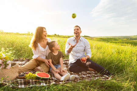 Excited dad juggling with apples, having fun and resting in nature with his family Banque d'images