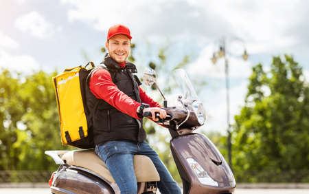 Delivering Food. Courier Man With Yellow Backpack Sitting On Moto Scooter Smiling To Camera Outside. Free Space