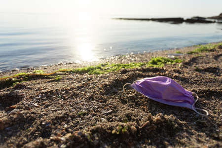 Ocean Pollution. Wasted Medical Mask Lying On Polluted Beach Outdoors. Ecological Background With Free Space For Text