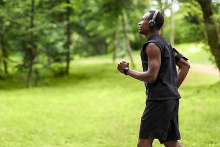 Profile photo of african american guy jogger training at city park, running towards copy space