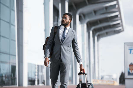 Black Businessman Traveler Walking With Suitcase Near Rail Station Or Airport Outdoors. Business Travel Concept