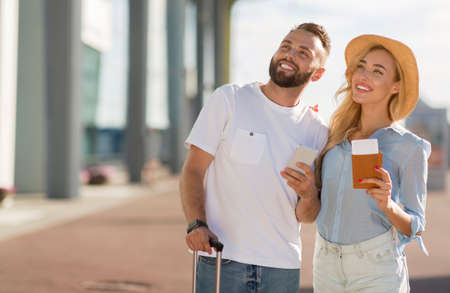Portrait of cheerful casual couple standing with valise outside, looking up, copy space, selective focus
