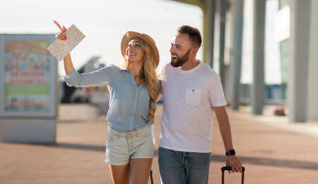 Two smiling young lovers with valise walking from airport in town, pointing up