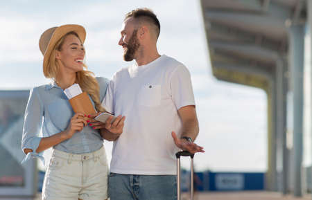Vacation Concept. Cheerful casual couple standing with valise outside, looking at each other, copy space