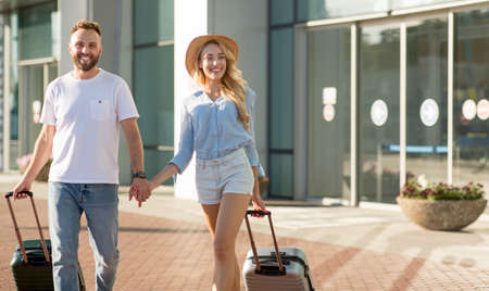 Full Of Joy Concept. Excited tourists walking near airport terminal, carrying valises and holding hands, copy space