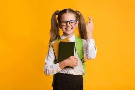 Schoolgirl Keeping Fingers Crossed For Luck In First School Day Standing On Yellow Background. Studio Shot