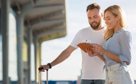 Ready For A Trip Concept. Cheeful couple holding their passports and tickets standing ouside with luggage