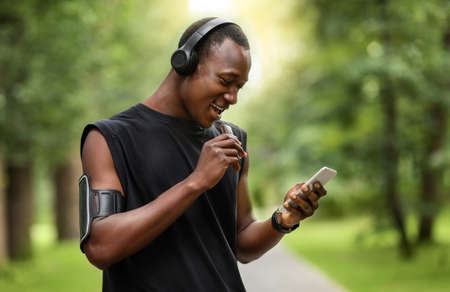 Cheerful african sportsman eating protein bar and using smartphone while resting, exercising at park, empty space