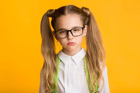 Sleepy Little Schoolgirl Tired Of School Homework Standing Over Yellow Studio Background. Back To School Routine.