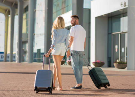 Traveling Together Concept. Rear view of two tourists walking in or out airport, carrying suitcases, holding hands