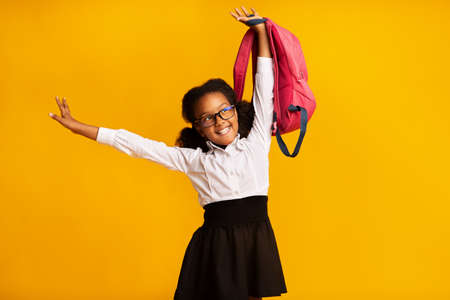 Back To School. Carefree African American Schoolgirl With Backpack Posing Over Yellow Background. Studio Shot