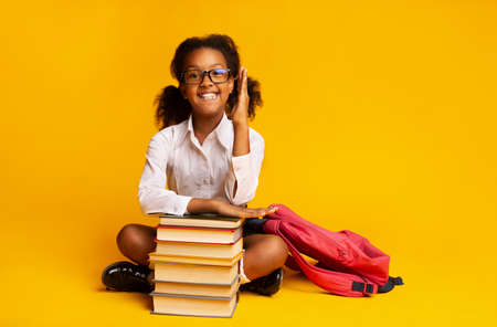 School Lesson. Clever African Schoolgirl Raising Hand Sitting At Book Stack Posing Over Yellow Studio Background. Copy Space 写真素材