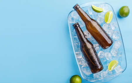 Summer, heat and beer mix. Two glass bottles without label in glass tray with ice and lime on blue background, top view, free space