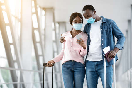 Black couple wearing medical masks waiting for departure in airport, using smartphone together, copy space