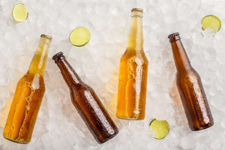 Various beers chilled for party. Cold glass bottles with light and dark beer without labels in ice with lime, free space Stock Photo