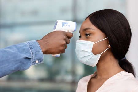 Security guard using digital medical electronic thermometer for black woman passenger in airport due to COVID-19, closeup