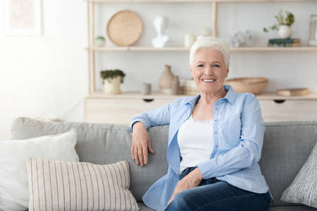 Relaxed Elderly Woman Posing On Couch Im Cozy Home Interior, Smiling At Camera, Free Space 스톡 콘텐츠