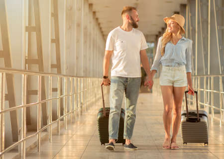 Romantic Travel. Loving couple walking with luggage in airport, holding hands and looking at each other, copy space