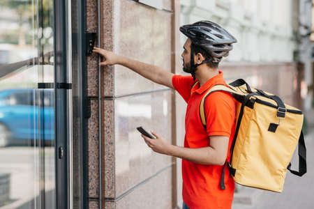 Young man with beard, with yellow big backpack and smartphone, ringing the bell near front door, free space