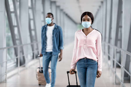Black Man And Woman Wearing Medical Masks Walking With Suitcases At Terminal, Selective Focus, Copy Space