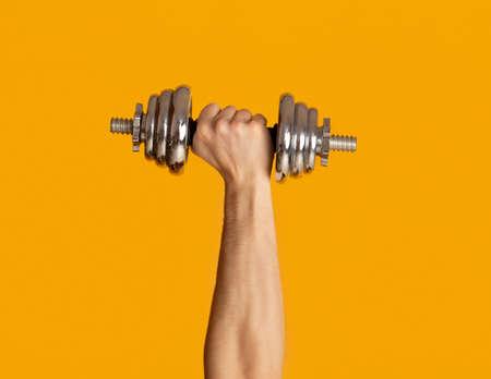Male hand lifting heavy dumbbell on orange background, close up