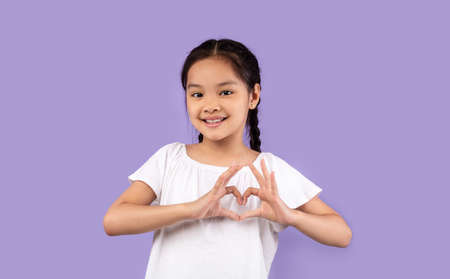 Love And Kindness. Little Asian Girl Gesturing Heart Shape Smiling To Camera Posing On Purple Studio Background.