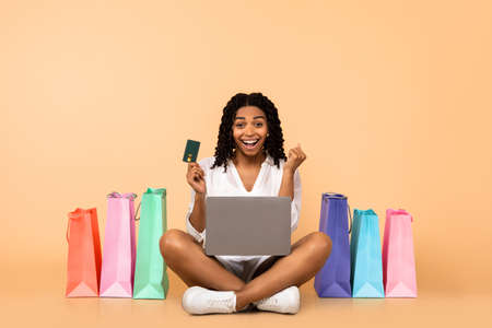 Black Lady With Laptop And Credit Card Shouting Shaking Fists Sitting Among Shopper Bags Over Beige Studio Background