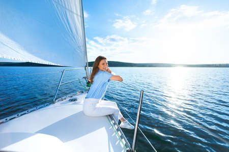 Woman Sitting On Yacht Deck Relaxing Looking At Sea Enjoying Summer Day On Water Sailing Outdoors. Dream Vacation. Copy Space Archivio Fotografico