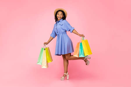Positive Black Woman Doing Shopping Posing With Colorful Shopper Bags Over Pink Background. Full Length, Studio Shot