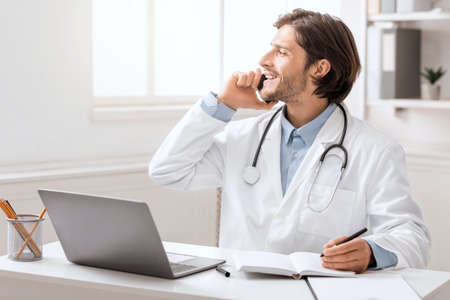 Positive young doctor talking with patient via cellphone at office, looking at free space