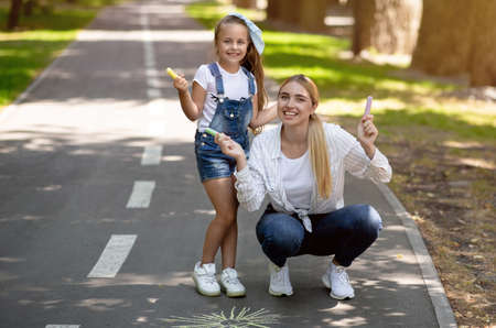 Mother And Daughter Posing Holding Chalks Drawing In City Park Outdoor. Weekend Leisure And Family Fun. Copy Space