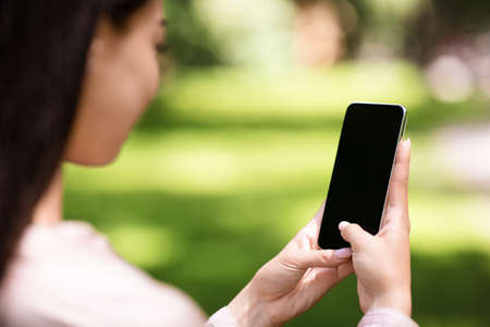 Woman using smartphone with blank black screen outdoors, mockup, over shoulder view with copy space for advertisement