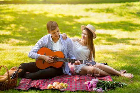 Affectionate young man playing guitar for his girl on romantic date at park Archivio Fotografico