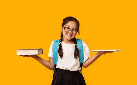 Asian School Girl Comparing Digital Tablet And Book Standing Over Yellow Studio Background. Foto de archivo