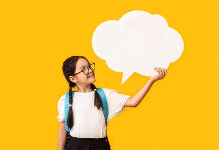 Asian Schoolgirl Holding Blank Speech Bubble Posing Over Yellow Studio Background. Mockup, Free Space