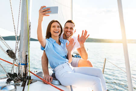 Couple On Yacht Making Selfie On Smartphone Enjoying Cruise Outdoors During Summer Vacation At Seaside. Free Space