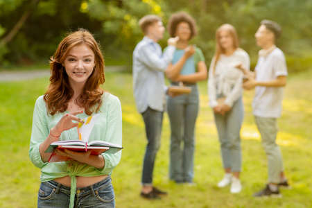 Portrait Of Smiling College Student Girl With Workbooks Posing Outdoors At Campus With Her Classmates On Background, Selective Focus