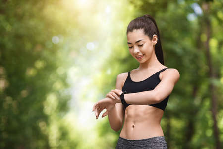 Smiling asian runner girl looking at heart rate monitor on smartwatch after jogging outdoors, checking fitness tracker, copy space