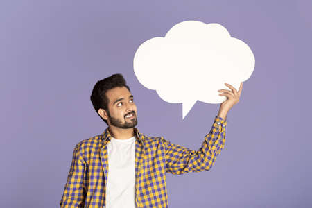 Handsome Indian man holding speech bubble with empty space for your design over lilac background