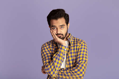 Handsome Indian man feeling bored or tired over lilac background