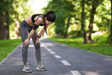 Exhausted Asian Jogger Girl Resting After Running On Path In Park, Free Space