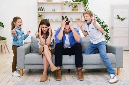 Naughty Kids Shouting Loudly Standing Near Tired Parents At Home. Family Problems And Difficult Parenting Concept.