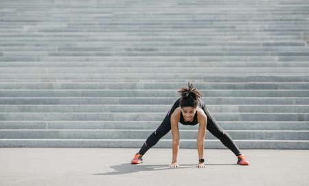 Exercises for flexibility outdoor. Joyful african american girl in sportswear with fitness tracker doing stretching near city stairs in morning