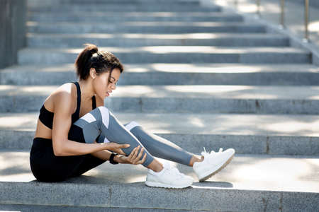 Upset african woman in sport clothes sitting on stairs, massaging ancle, side view, empty space