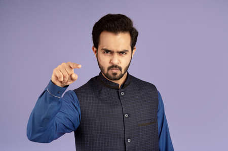 Angry Indian man pointing finger at screen in accusation on violet background